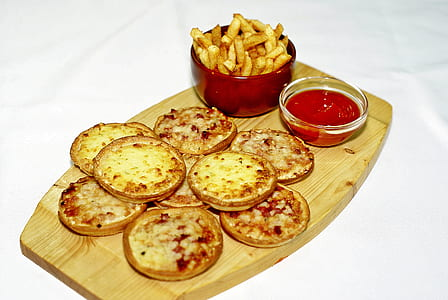 assorted-flavor of pizza with fries and ketchup on brown wooden tray