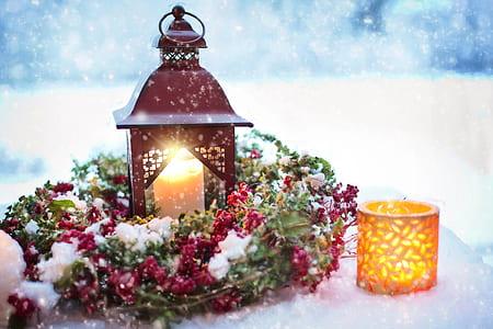 white pillar candle in red lantern during winter
