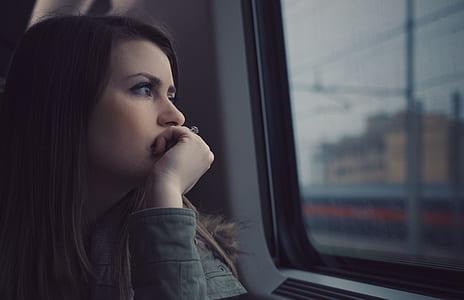woman wearing gray jacket looking on window
