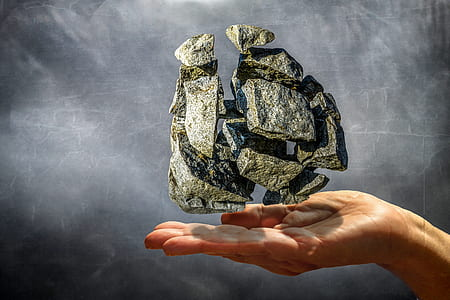 person's hand with rock floating over illustration