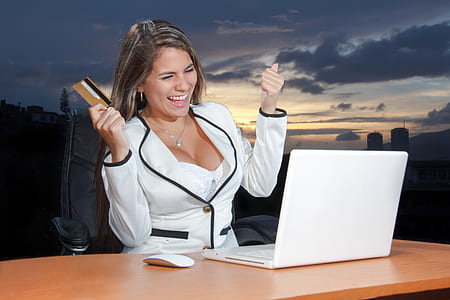 woman in white blazer holding card while looking at MacBook white