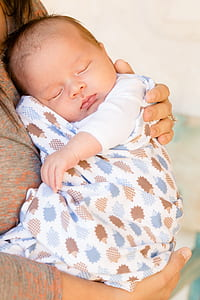 baby in white, blue, and brown swadder