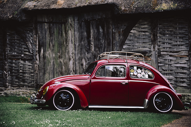red Volkswagen Beetle parked on grass beside gray wooden cabin