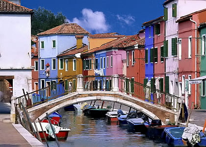 boat under arch bridge on a canal near assorted-color concrete houses