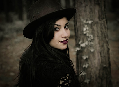 woman wearing black hat staring and smiling at the camera