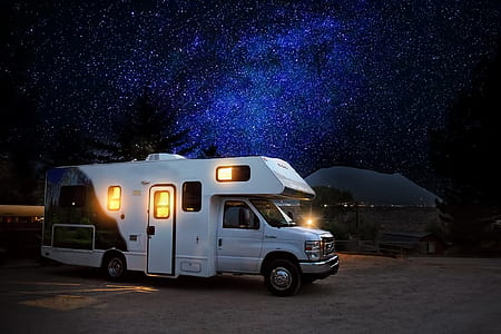 white RV beside the shore under blue and black skies