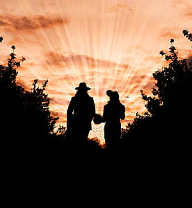 Silhouette Photo of Man and Woman Wearing Hat Standing Between Trees during Golden Hour