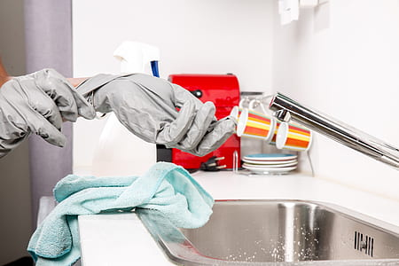 person wearing gloves near stainless steel faucet