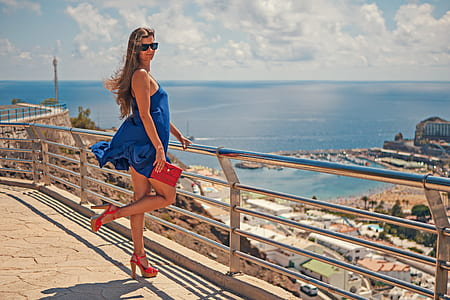 woman in blue sleeveless dress holding on stainless steel rail
