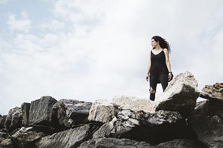woman wearing black sleeveless dress standing on a rock