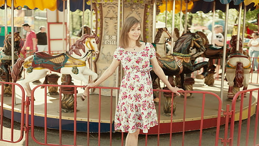 woman in white and pink floral dress near carousel