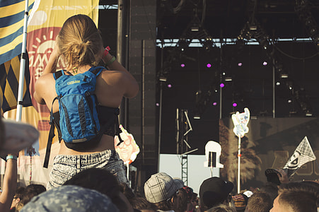 woman piggyback ride wearing blue backpack near stage