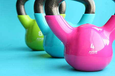 three pink , blue, and green kettle bells