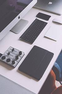 silver iMac, Apple cordless keyboard, traction pad, silver Macbook, and tablet case on white table