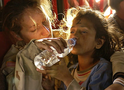 woman helping the girl drinking water on plastic bottle
