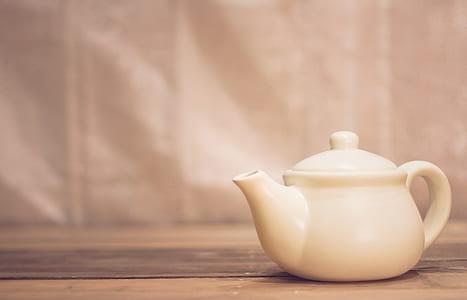 white ceramic teapot on brown surface