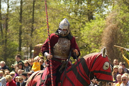 man in red and gray knight suit riding horse in red and black textile