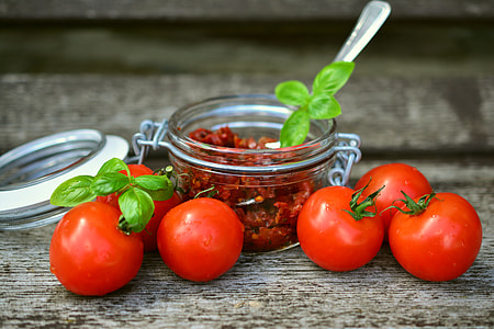 tomatoes and airtight jars with chili inside
