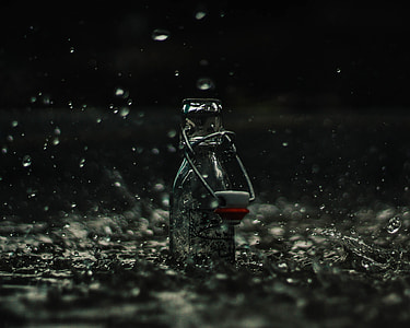 photo of clear glass bottle during rain