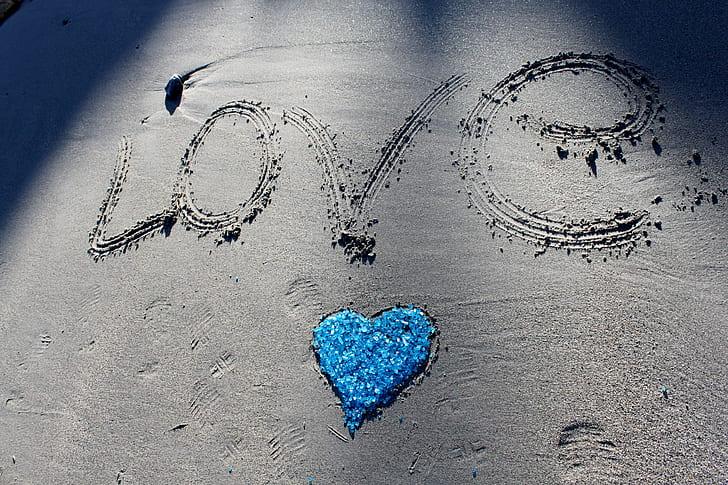 Love illustration on sand during daytime