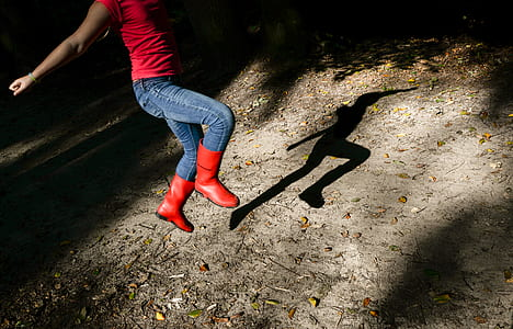 Photography of a Girl in Red Shirt With Blue Denim Jeans and Red Leather Wide-calf Boots Jumping