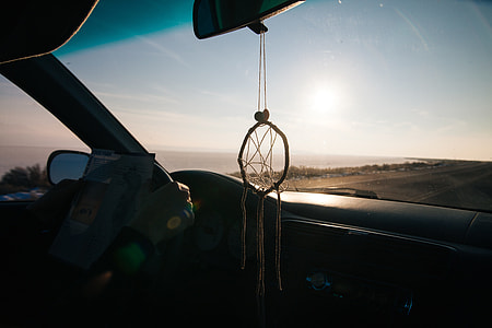 dreamcatcher hanged from rear view mirror inside car driving on road along shore during golden hour