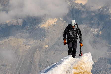 man wearing jacket walking on mountain covered in ice