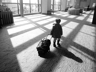 boy with luggage walking inside room
