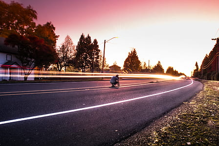 Person Sitting on Black Top Road during Twilight