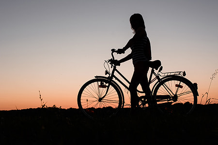 A silhouette of a woman with a bicycle at sunset