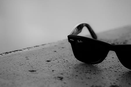 greyscale photo of black Ray-Ban Wayfarer sunglasses