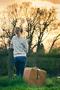 woman wearing gray long-sleeved shirt and blue jeans beside brown travel luggage