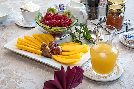 assorted fruits on plate and glass bowl