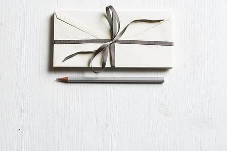 envelope card beside gray pencil