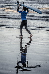 person carrying blue surfboard