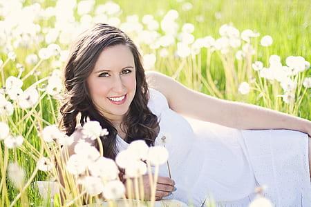 woman wearing white dress lying on flower fields