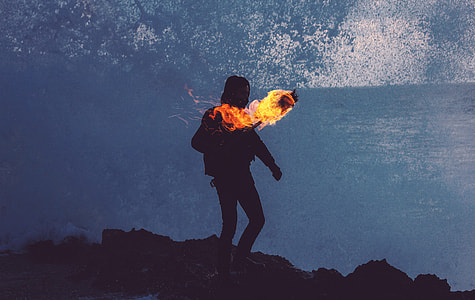 person standing on the mountain holding torch with fire
