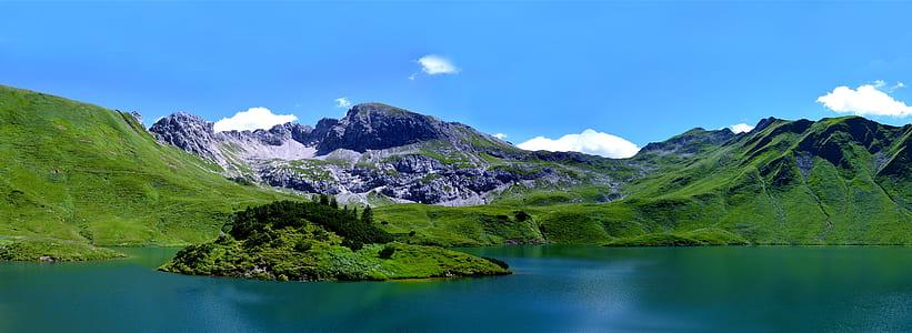 body of water beside green mountain