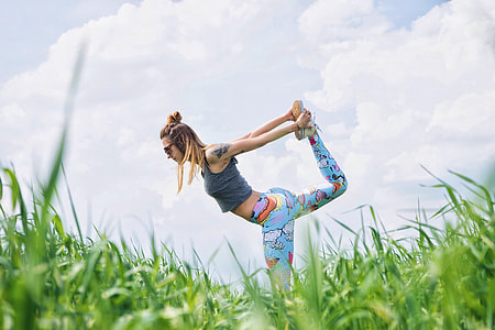 woman in gray crop top dancing on grass field during daytime