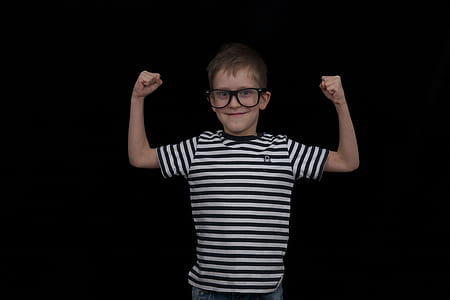 boy raising his hand wearing eyeglasses