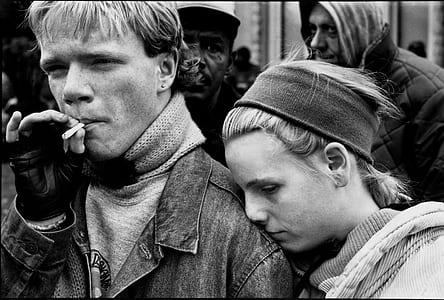 grayscale photo of man smoking near woman