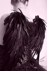 woman wearing black dress with wings