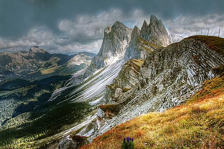 white and green mountain under dark clouds