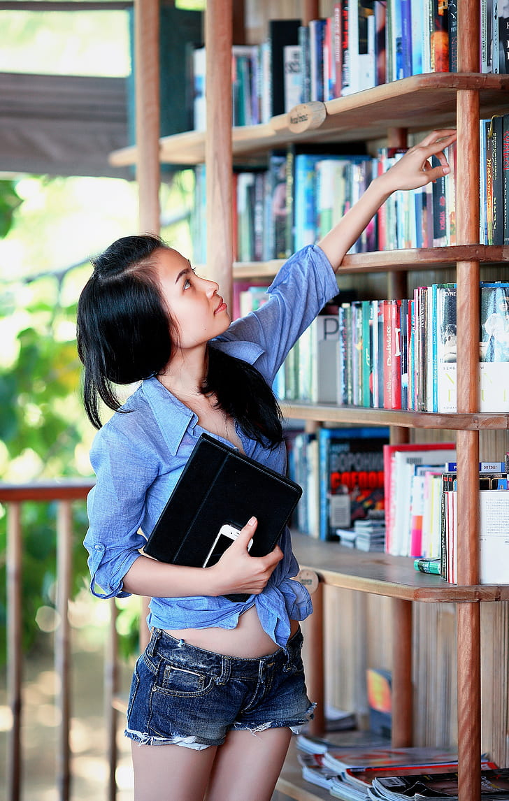 woman with blue sport shirt reaching of a book on a bookcase
