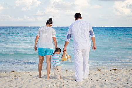 mother, father, and child walking on sea shore during daytime