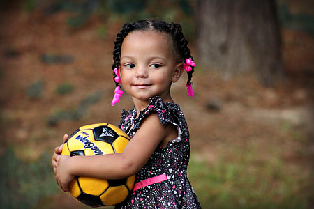 girl hugging yellow and black soccer ball