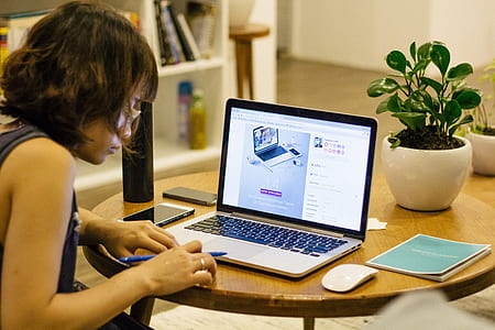 woman sitting in front of MacBook Pro