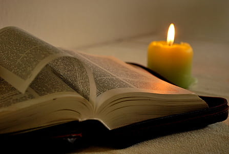 lighted yellow candle near opened book