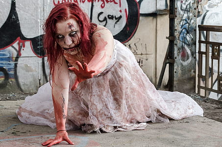 woman in white bridal gown full of fake blood crawling on floor