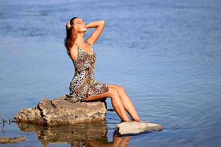 woman sit on rock surrounded by water at daytime